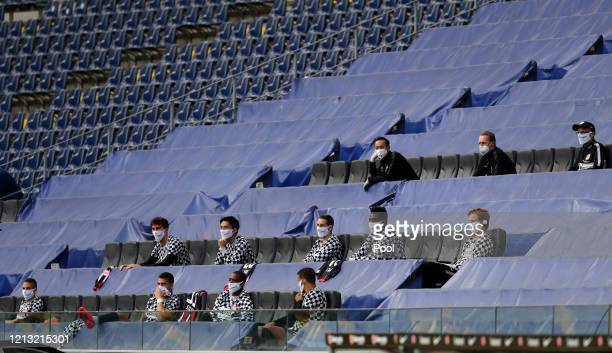 Frankfurt's team members keeping a distance sit in the stands during the Bundesliga match between Eintracht Frankfurt and Borussia Moenchengladbach...
