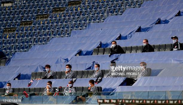 Frankfurt's team members keeping a distance sit in the stands during the German first division Bundesliga football match Eintracht Frankfurt v...