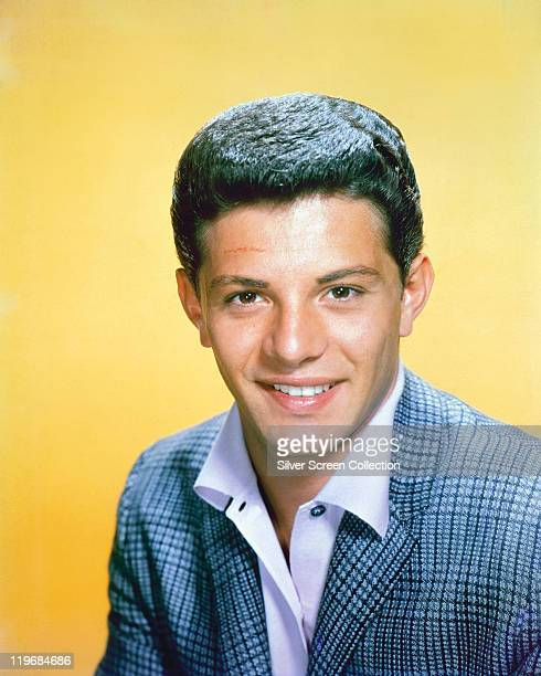 Frankie Avalon US singer and actor wearing a blue tweed jacket in a studio portrait against a yellow background circa 1960