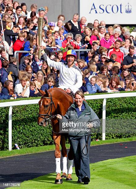 Frankie Dettori carries the Olympic torch whilst riding former race horse Monsignor around the parade ring on day 53 of the London 2012 Olympic Torch...