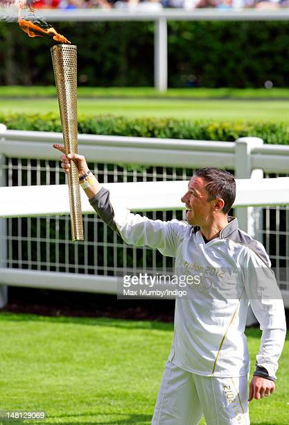 Frankie Dettori holds the Olympic torch after carrying it around the parade ring whilst riding former race horse Monsignor on day 53 of the London...