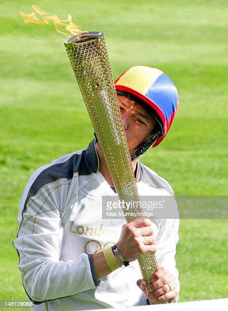Frankie Dettori kisses the Olympic torch after carrying it around the parade ring whilst riding former race horse Monsignor on day 53 of the London...