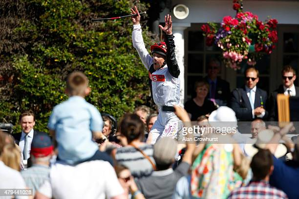 Frankie Dettori leaps from Golden Horn in the winners enclosure after winning The Coral Eclipse as a large crowd look on at Sandown racecourse on...