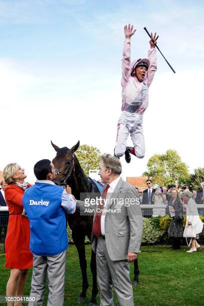 Frankie Dettori leaps from Too Darn Hot after they win The Darley Dewhurst Stakes at Newmarket Racecourse on October 13 2018 in Newmarket United...