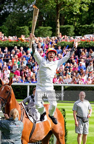 Frankie Dettori performs his flying dismount from former race horse Monsignor after carrying the Olympic torch around the parade ring on day 53 of...