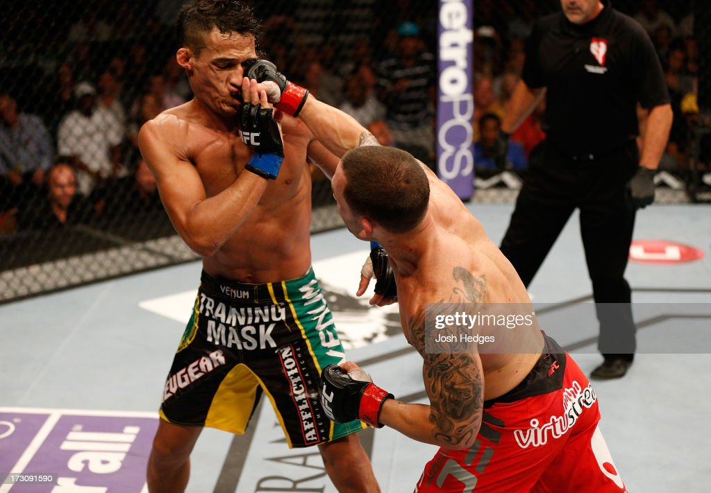 Frankie Edgar punches Charles Oliveira in their featherweight fight during the UFC 162 event inside the MGM Grand Garden Arena on July 6, 2013 in Las Vegas, Nevada.