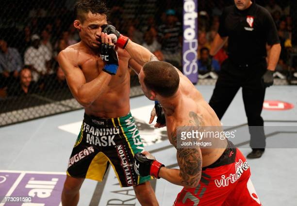 Frankie Edgar punches Charles Oliveira in their featherweight fight during the UFC 162 event inside the MGM Grand Garden Arena on July 6 2013 in Las...