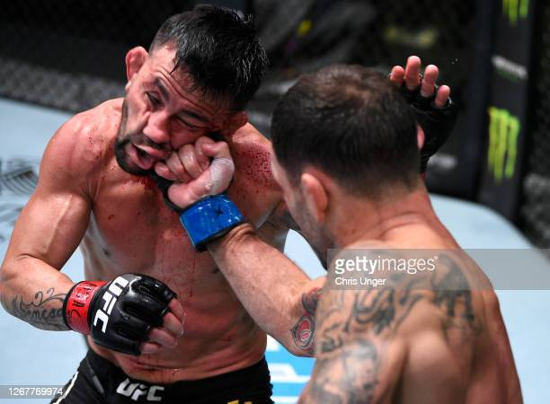 Frankie Edgar punches Pedro Munhoz of Brazil in their bantamweight fight during the UFC Fight Night event at UFC APEX on August 22, 2020 in Las...