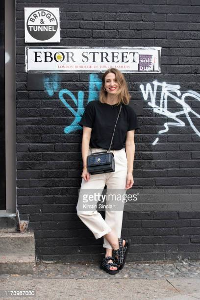 Frankie Graddon wears a black T shirt Cream rolled up jeans with a Kurt Geiger bag and shoes on August 23 2019 in London England