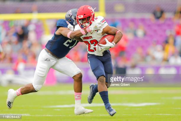 Frankie Hickson of the Liberty Flames is tackled during a run by Kenderick Duncan Jr #27 of the Georgia Southern Eagles during the second quarter of...