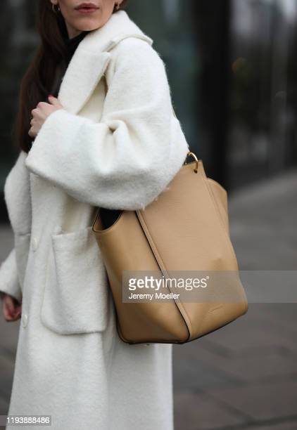 Frankie Miles wearing Bally loafer, Uniqlo x JW Anderson pants, Wolford Body, Weekday coat and Cochinelle bag on December 12, 2019 in Berlin, Germany.