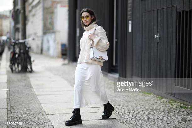 Frankie Miles wearing knit gestuz, Slip skirt Zara, Yellow Sunglasses vogue eyewear, Boots Dr martens, White Bag furla mimi on March 19, 2019 in...