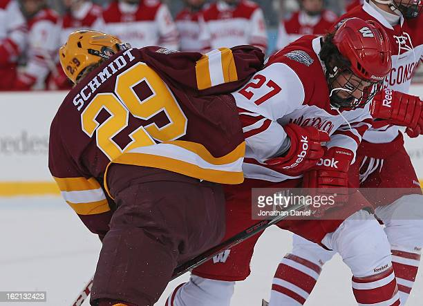 Frankie Simonelli of the Wisconsin Badgers hits Nate Schmidt of the Minnesota Golden Gophers during the Hockey City Classic at Soldier Field on...