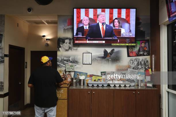 Franklin Araujo works at the El Original EL Arepazo restaurant as a television broadcasts US President Donald Trump as he delivers his State of the...