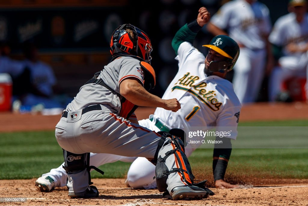 Franklin Barreto #1 of the Oakland Athletics is tagged out at home plate by Nick Hundley #5 of the San Francisco Giants during the third inning at the Oakland Coliseum on July 22, 2018 in Oakland, California. The Oakland Athletics defeated the San Francisco Giants 6-5 in 10 innings.