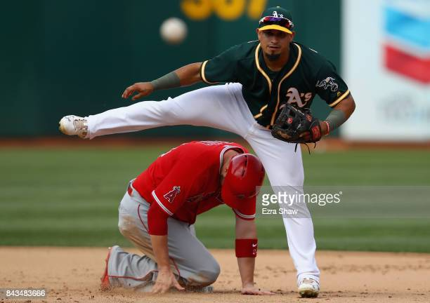 Franklin Barreto of the Oakland Athletics tries to turn a double play as CJ Cron of the Los Angeles Angels slides in to second base on a ball hit by...