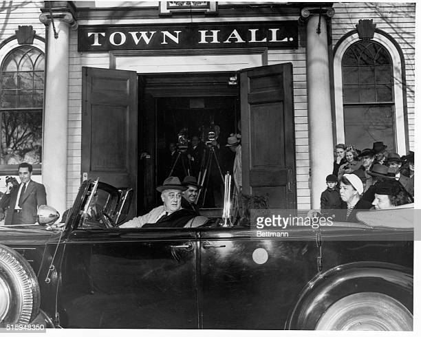 Franklin D Roosevelt sits in a car outside Town Hall with his dog Fala his wife Eleanor and another woman