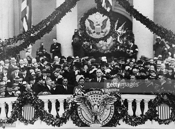 Franklin Delano Roosevelt making his inaugural address as 32nd President of the USA. Beneath his is the American symbol of an eagle with its wings...