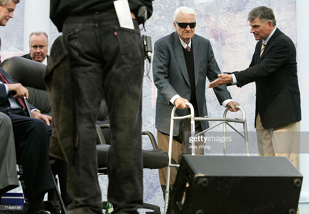 Franklin Graham (R) shows his father evangelist Billy Graham (2nd R) where his seat is during the Metro Maryland 2006 Festival July 9, 2006 at Oriole Park at Camden Yards in Baltimore, Maryland. Franklin Graham led the three-day-program filled with music, prayers and gospel messages.