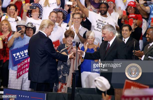 Franklin Graham son of evangelist Billy Graham is greeted by US President Donald Trump during a Trump rally on August 22 2017 in Phoenix Arizona