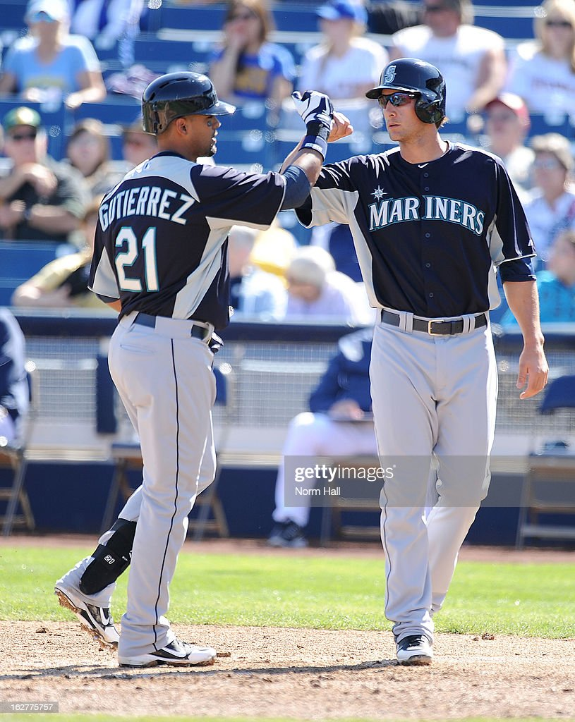 Franklin Gutierrez #21 of the Seattle Mariners and teammate Vinnie Catricala #36 celebrate a home run against the Milwaukee Brewers at Maryvale Baseball Park on February 26, 2013 in Maryvale, Arizona.