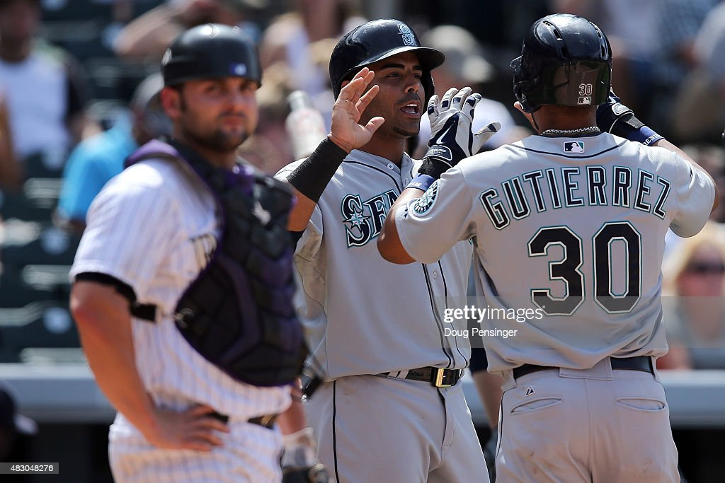 Franklin Gutierrez #30 of the Seattle Mariners celebrates his two run home run with Nelson Cruz #23 of the Seattle Mariners as catcher Michael McKenry #8 of the Colorado Rockies looks on as the Mariners take a 5-3 lead in the seventh inning during interleague play at Coors Field on August 5, 2015 in Denver, Colorado. McKenry would go on to hit the game winning walk off home run as the Rockies defeated the Mariners 7-5 in 11 innings.