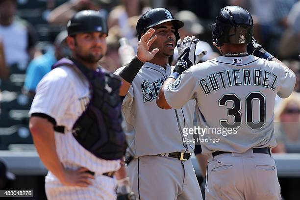 Franklin Gutierrez of the Seattle Mariners celebrates his two run home run with Nelson Cruz of the Seattle Mariners as catcher Michael McKenry of the...