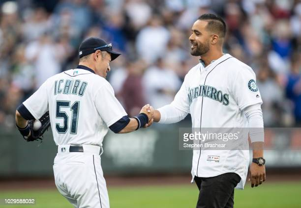 Franklin Gutierrez shakes hands with Ichiro Suzuki of the Seattle Mariners after throwing out the ceremonial first pitch before a game against the...