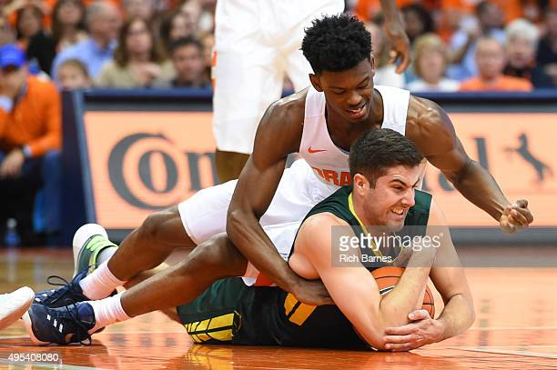 Franklin Howard of the Syracuse Orange and Connor Mahoney of Le Moyne Dolphins battle for control of the ball during the first half at the Carrier...