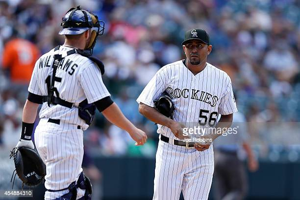 Franklin Morales and Jackson Williams of the Colorado Rockies talk in between pitches against the San Diego Padres during the game at Coors Field on...