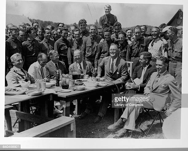 Franklin Roosevelt and other administration officials visit a Civilian Conservation Corps Camp during the New Deal.