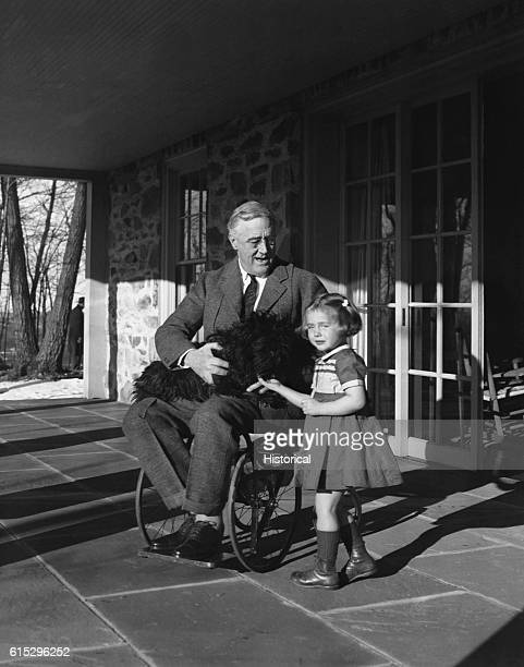 Franklin Roosevelt holds his Scotch terrier Fala on his lap as he talks to Ruthie Bie the daughter of the Hyde Park caretaker Roosevelt is sitting on...
