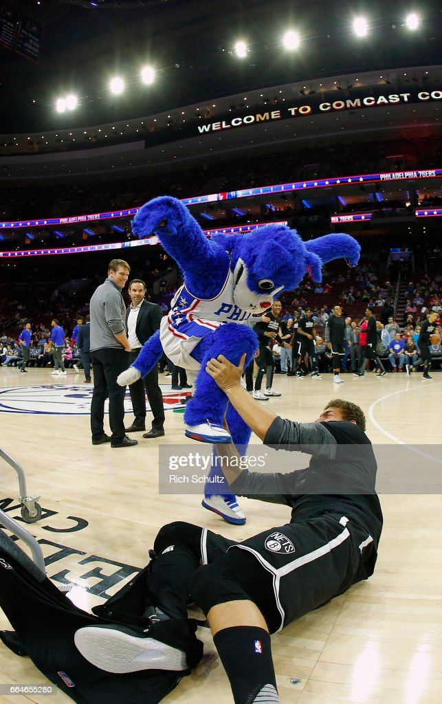 Franklin the Dog, mascot of the Philadelphia 76ers wrestles with Brook Lopez #11 of the Brooklyn Nets before the start of an NBA game at Wells Fargo Center on April 4, 2017 in Philadelphia, Pennsylvania.. The Nets defeated 76ers 141-118.