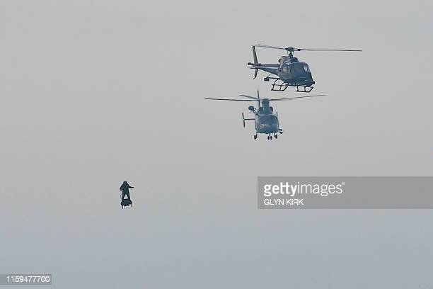Franky Zapata moves with his jetpowered Flyboard next to helicopters as he arrives at St Margaret's Bay in Dover on August 4 during his attempt to...