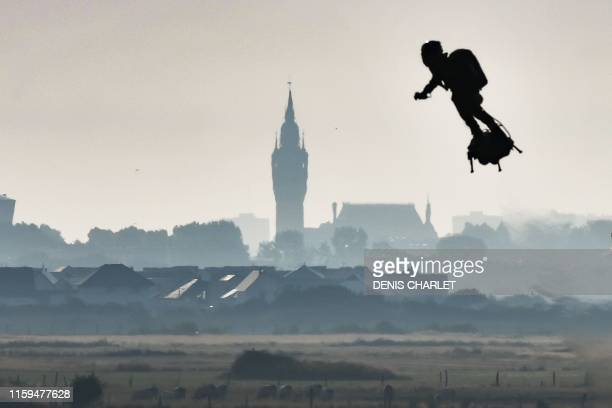 """Franky Zapata on his jet-powered """"flyboard"""" flies past the belfry of the city hall of Calais after he took off from Sangatte, northern France, on..."""