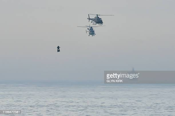 """Franky Zapata stands on his jet-powered """"flyboard"""" next to helicopters as he arrives at St. Margaret's Bay in Dover, on August 4 during his attempt..."""