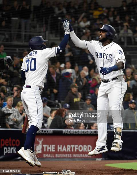 Franmil Reyes of the San Diego Padres is congratulated by Eric Hosmer after hitting a solo home run during the third inning of a baseball game...