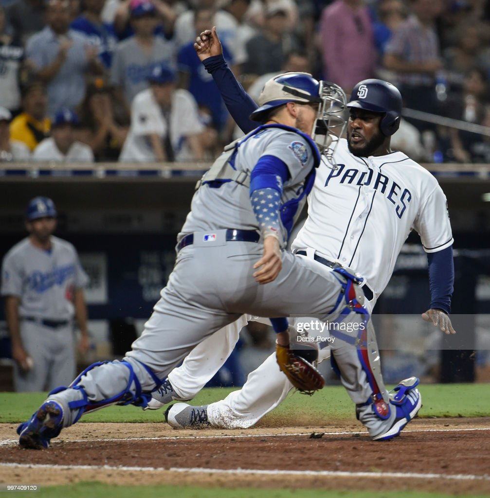 Franmil Reyes #32 of the San Diego Padres scores ahead of the tag of Yasmani Grandal #9 of the Los Angeles Dodgers during the seventh inning of a baseball game at PETCO Park on July 12, 2018 in San Diego, California.