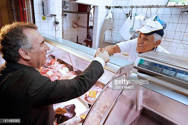 François Bayrou President of the MoDem centrist party and candidate for the 2012 French presidential election shakes hands with a butcher as he...