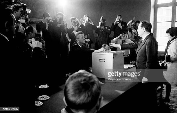 François Mitterrand déposant son bulletin de vote dans l'urne sa femme Danielle derrière lui dans le bureau de vote à la mairie de ChateauChinon...