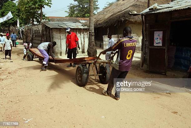 Franois TILLINAC 'En Casamance dans un village de departs de clandestins vers les Canaries' People wheel a plank for the construction of a boat 08...