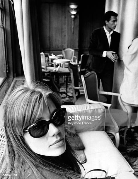 Françoise Hardy dans les salons du cabaret du Savoy Hotel en arrièreplan son fiancé JeanMarie Perrier à Londres RoyaumeUni le 7 juin 1965