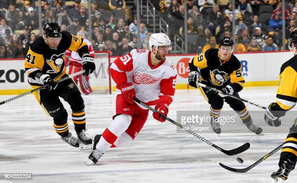 Frans Nielsen of the Detroit Red Wings handles the puck against Daniel Sprong and Jake Guentzel of the Pittsburgh Penguins at PPG Paints Arena on...
