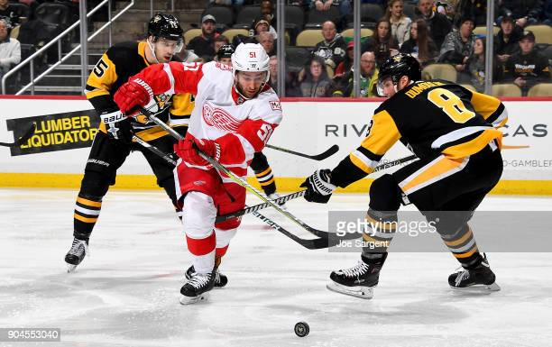 Frans Nielsen of the Detroit Red Wings handles the puck between Riley Sheahan and Brian Dumoulin of the Pittsburgh Penguins at PPG Paints Arena on...