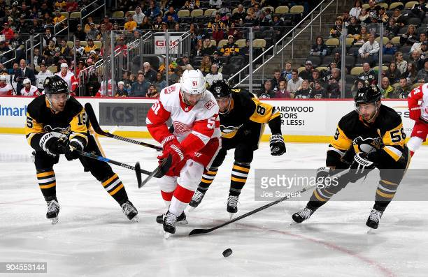 Frans Nielsen of the Detroit Red Wings handles the puck between Riley Sheahan Kris Letang and Brian Dumoulin of the Pittsburgh Penguins at PPG Paints...