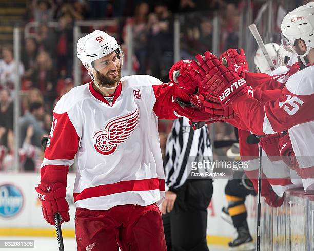 Frans Nielsen of the Detroit Red Wings pounds gloves with teammates on the bench following his game winning shootout goal during an NHL game against...