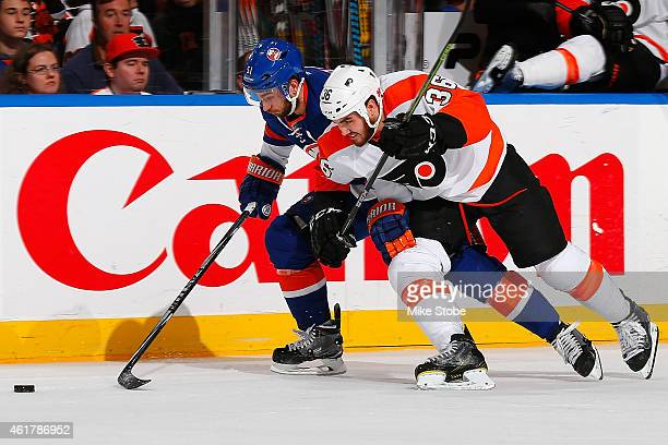 Frans Nielsen of the New York Islanders chases down a loose puck under pressure from Zac Rinaldo of the Philadelphia Flyers at Nassau Veterans...