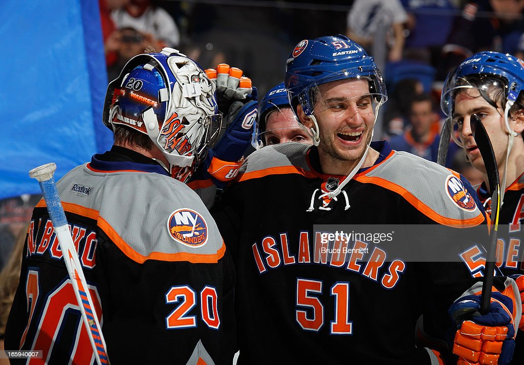 Frans Nielsen #51 of the New York Islanders congratulates Evgeni Nabokov #20 on their victory over the Tampa Bay Lightning at the Nassau Veterans Memorial Coliseum on April 6, 2013 in Uniondale, New York. The Islanders defeated the Lightning 4-2.