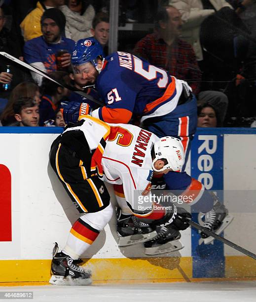 Frans Nielsen of the New York Islanders is checked by Dennis Wideman of the Calgary Flames during the second period at the Nassau Veterans Memorial...
