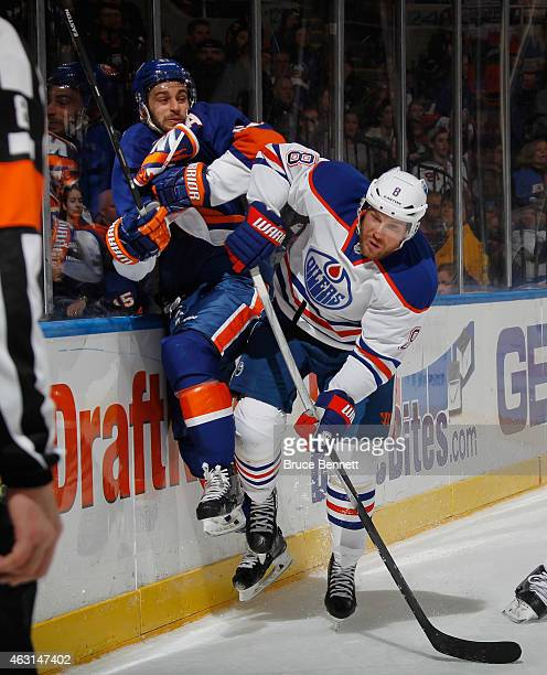 Frans Nielsen of the New York Islanders is hit into the boards by Derek Roy of the Edmonton Oilers during the second period at the Nassau Veterans...